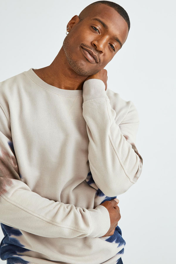African American Model wearing a richer Poorer Sweat Shirt